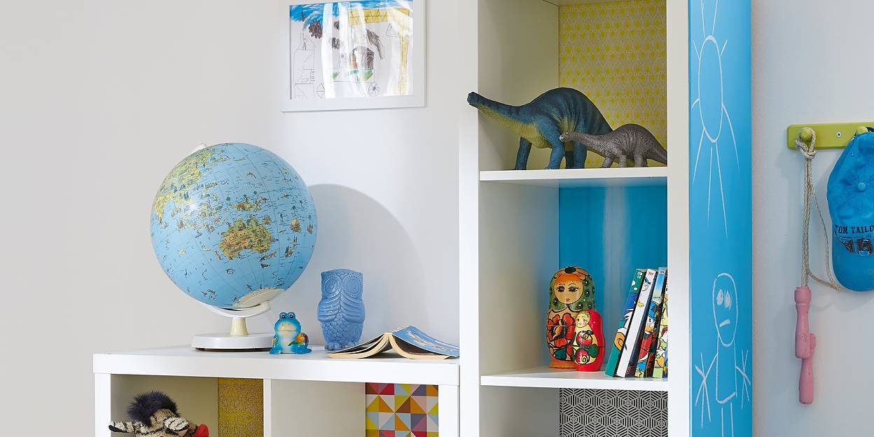 Here's an idea that kids will love. Each shelf has its own background, using decorative paper, stuck with tesa® Spray Glue PERMANENT, and on the side of the unit, there's a big blackboard so they're free to write or paint.
