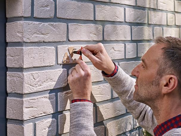 Applying the adhesive to the tesa® Adhesive Screw Triangular for Brick & Stone