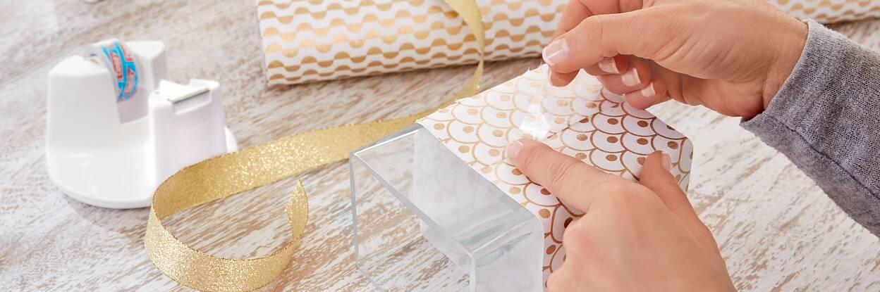 Schlichte Glasvasen sind schön, aber manchmal auch ein bisschen langweilig. Da können Geschenkpapier und passendes -band ganz schnell Abhilfe schaffen. Einfach den Umfang der Vasen ausmessen, Papier und Band entsprechend zuschneiden, um die Vase legen und auf der Rückseite mit tesafilm® fixieren. Mal ehrlich: Einfacher geht's doch wirklich nicht!