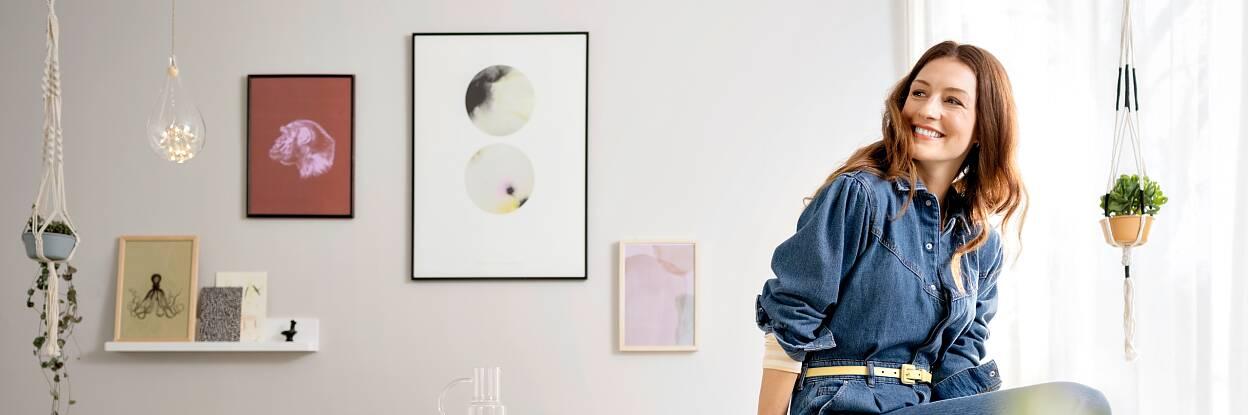 Wohnzimmer gestalten - Frau sitzt lachend auf der Kante eines Tisches, im Hintergrund Bilder