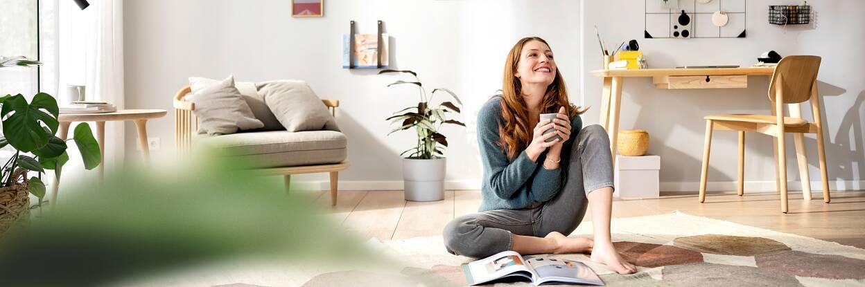 Wohnzimmer organisieren - Teaser: Frau sitzt lachend auf dem Boden im Wohnzimmer