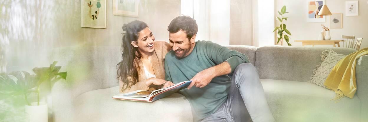 Entspannt wohnen - Teaser: Blick durch die Fensterscheibe auf lachendes Pärchen im Wohnzimmer