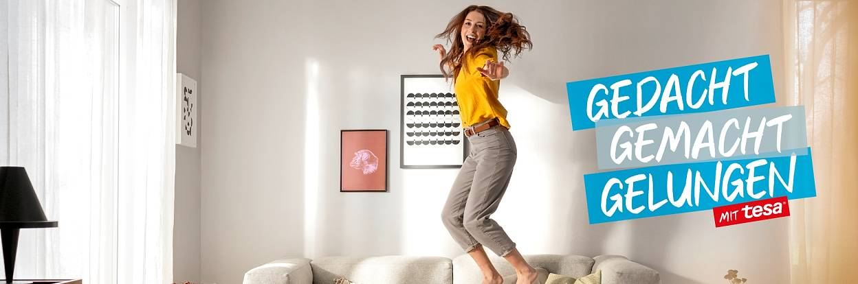 Wohnzimmerideen Header: Frau springt glücklich lachend auf dem Sofa