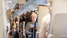 Blonde casual caucasian lady traveling by train. Train full of passengers going to work by public transport at rush hour. Adobe stock image