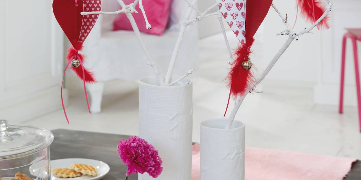 Homemade paper hearts hang in the bouquet made of branches painted white for Valentine's Day.