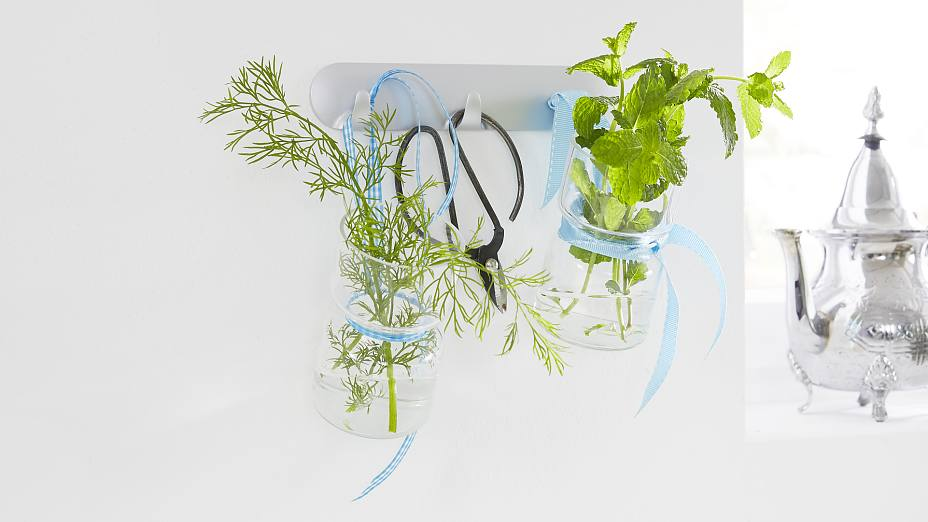 Lovely kitchen accessories: culinary herbs in glass jars - a practical kitchen decor. With the tesa Powerstrips® Hook Rack, it is easy to mount this unique kitchen storage.
