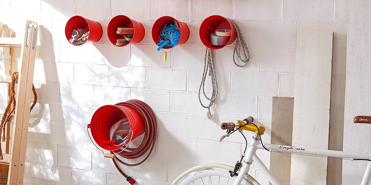 Garden hose storage made out of wall-mounted buckets