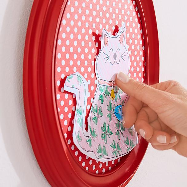 Mounting children's art work in frames when making a DIY gallery wall using double-sided adhesive pads for transparent & glass.