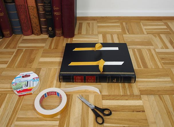 Image of book with protective film being removed from tesa® Powerbond double-sided adhesive tape.