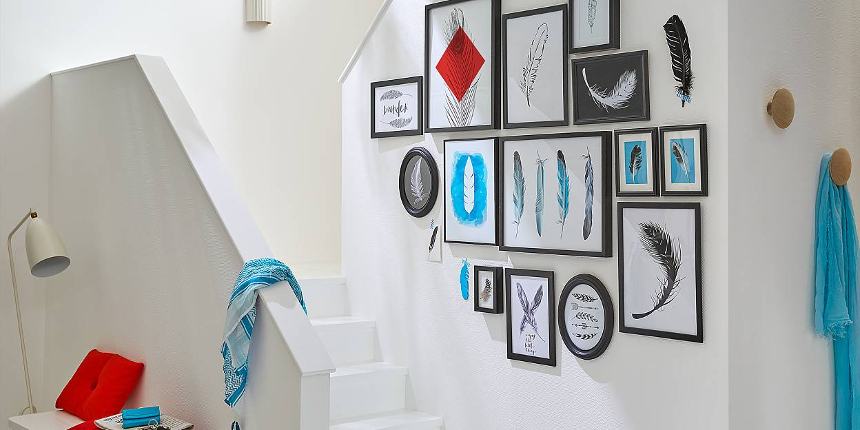 A group of pieces of art in frames of various sizes is a great idea for a transitional space like a staircase.