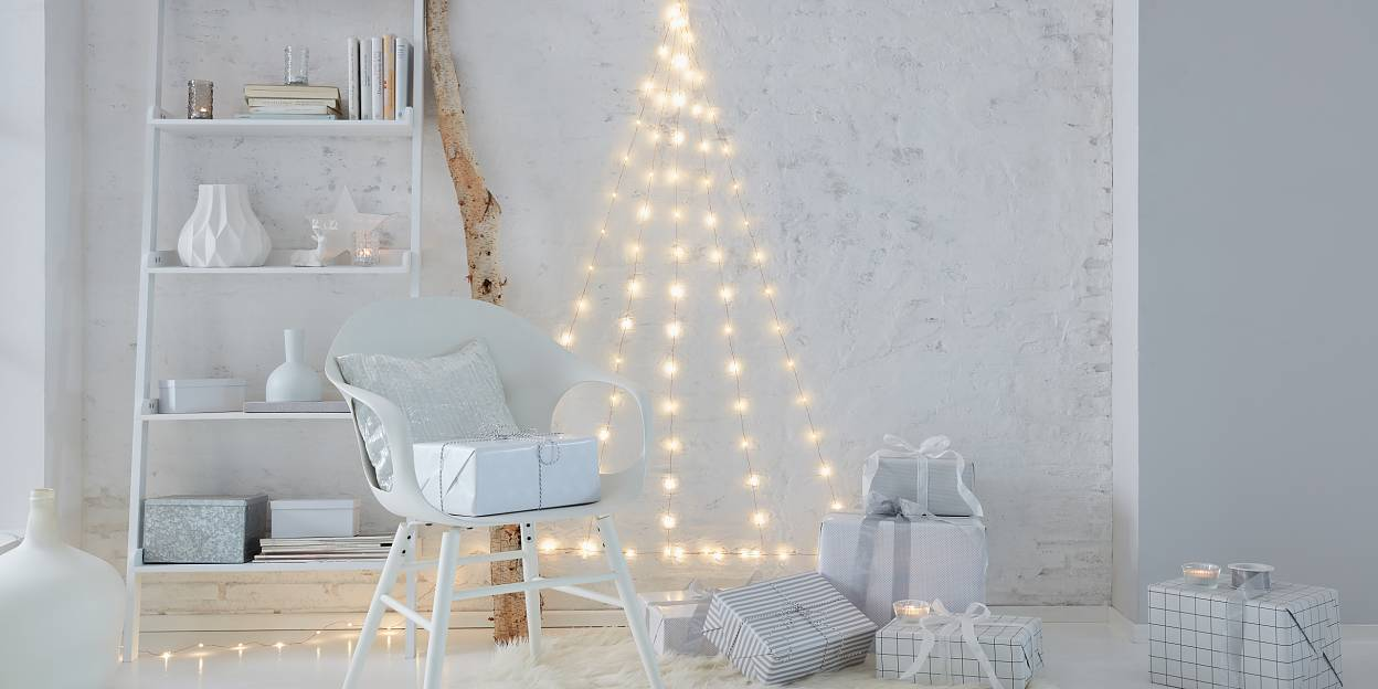 Needleless and extremely low-maintenance: A Christmas tree that doesn't need decorations. Create the tree with LED fairy lights that are fixed to the wall with transparent hooks.