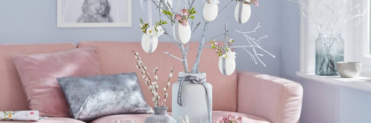 Auf die Idee muss man erst einmal kommen: Der Osterhase hat sich Gänseeier organisiert und sie ohne viel Aufwand zu kleinen Vasen umfunktioniert, die mit Blumen gefüllt in grau besprühten Ästen hängen.