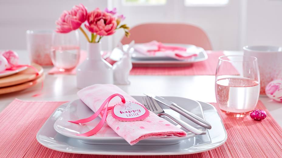 Pink is the main color on this Easter table. The bunny napkin folds each wear a matching DIY napkin ring with a bunny portrait and good wishes for the spring holidays.