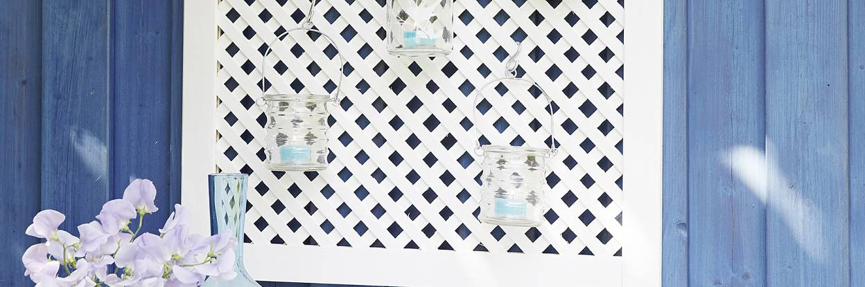 A simple lattice screen door can be transformed into a flower pot or lantern holder with tesa Powerbond® OUTDOOR and a little bit of imagination. This outdoor tape is weather resistant, making it perfect for garden fixing.