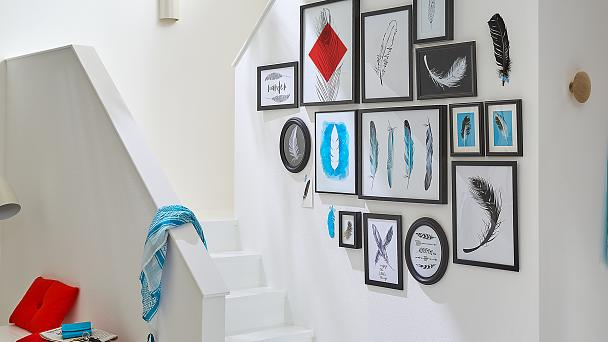 A group of pieces of art in frames of various sizes is a great idea for a transitional space like a staircase. Choose a common theme to create this display. It's quick to do and you won't need any tools.